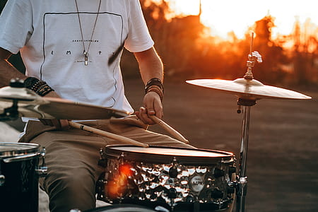 photography of man playing drum during golden hour