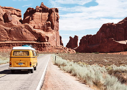 yellow van traveling on concrete road towards red rock monoliths during daytime