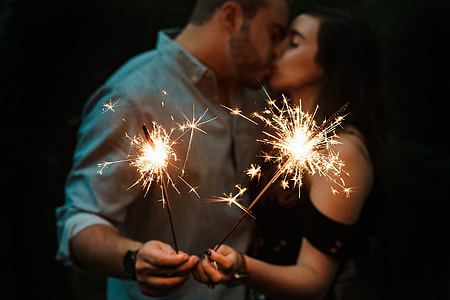 man and woman kissing while holding spark firecrakers