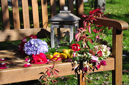 closeup photography of gray candle lantern on bench surrounded with flowers