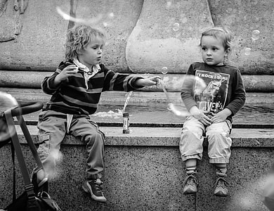 two boys near fountain grayscale photo