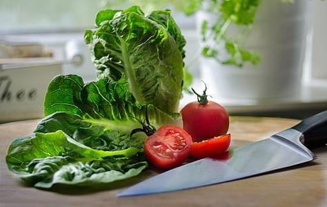tomato and green leafy vegetable beside black handled knife