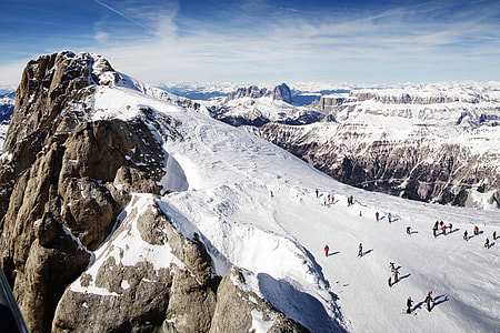 Landscape shot of people skiing on the snow slopes of the Dolomite mountains in Italy
