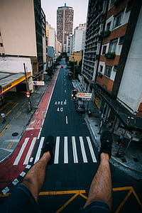 Person Wearing Black Lace Up Sneakers Facing Gray Concrete Road Top Between Concrete Buldings