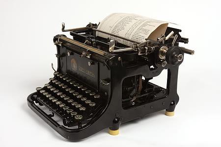 black typewriter with printer paper