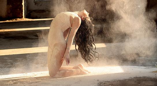 woman in leotards kneeling while bending head over back