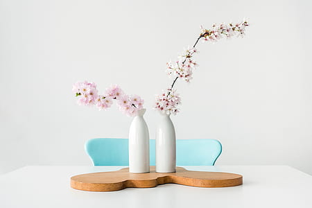 white and pink flowers on white ceramic vases