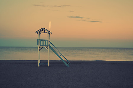 white and blue lifeguard house during golden hour