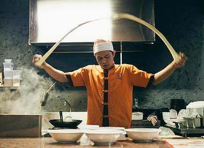 person in orange and black chef uniform baking