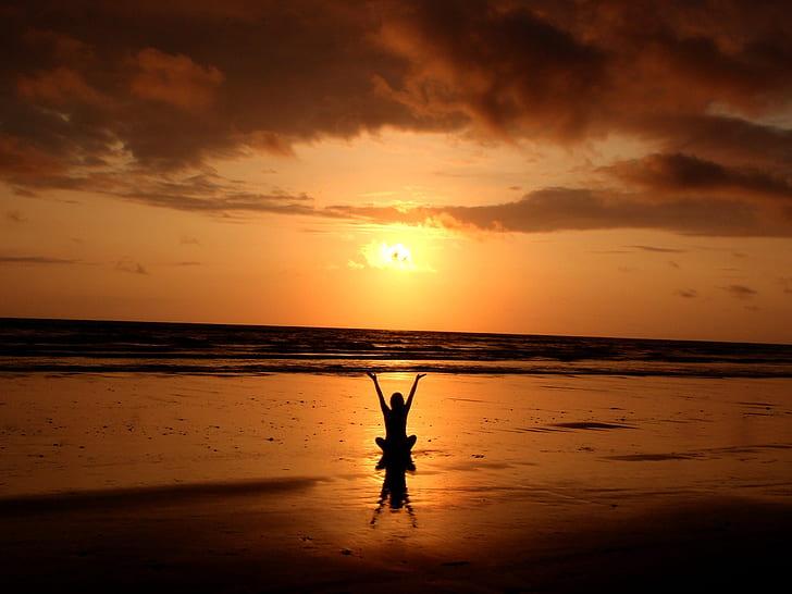 silhouette person sitting near beach shore