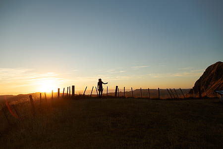 silhouette of man near the fence during golden hour
