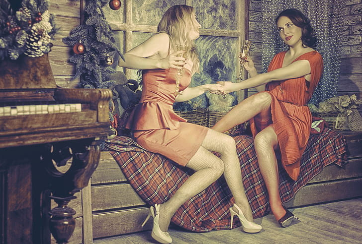two woman wearing red dress