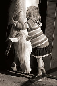 grayscale photo of girl hugging white horse