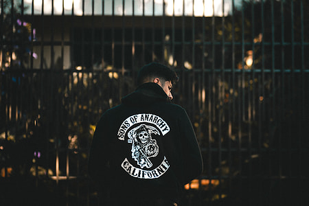 person in black and white jacket in front of gate