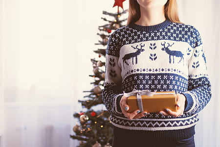 woman wearing blue and white sweater holding gift box