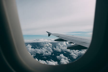 photo of plane wing and clouds