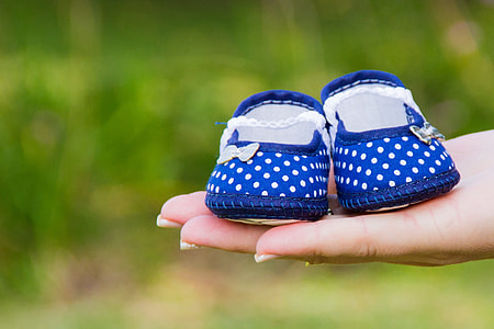 pair of blue crib shoes on top of person's hand