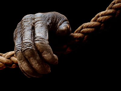 right human hand on brown rope