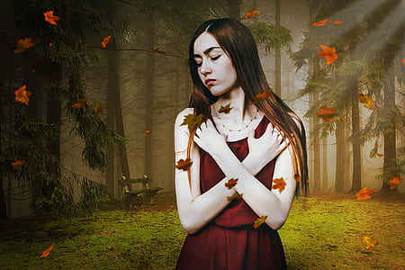 woman wearing red dress standing with falling leaves at forest