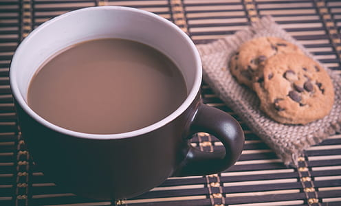 black ceramic mug filled with chocolate near cookies