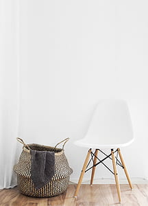 white and brown chair beside fabric clothes basket