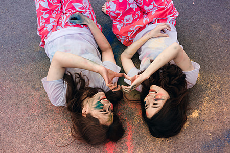 two women laying on floor doing heart sign together