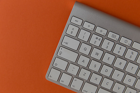 Apple wireless computer keyboard on orange background