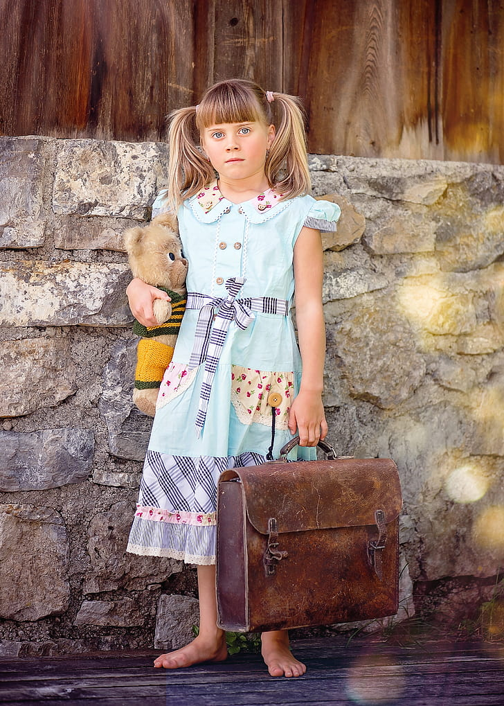 girl carrying suitcase and bear plush toy