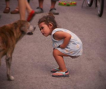 girl in blue sleeveless dress beside brown dog