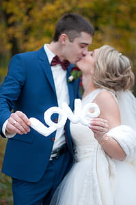 Newly Wed Couple Kissed Each Other While Holding Love Cutout