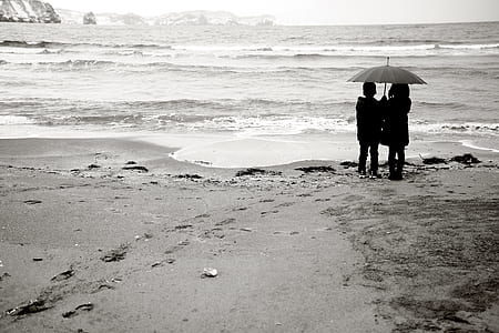 gray scale photo of two girls holding gray umbrella standing beside body of water