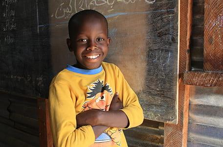 boy standing beside chalkboard