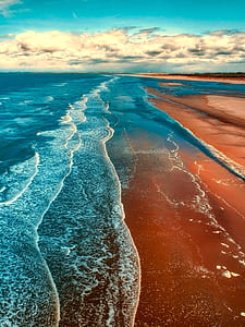 blue sea with brown sand