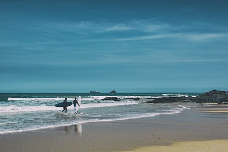 Two surfers walk along the beach on a sunny day on the coast of Cornwall in England