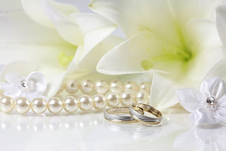 silver-colored rings and white pearl necklace