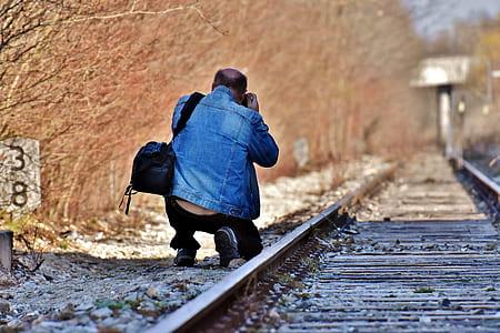 man wearing blue denim jacket and black pants kneeling beside train rail holding camera during daytime