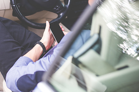 Business Manager Using His Phone in a Car