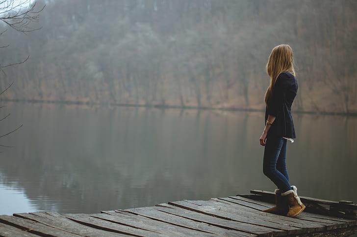 woman standing in wooden pier near lake