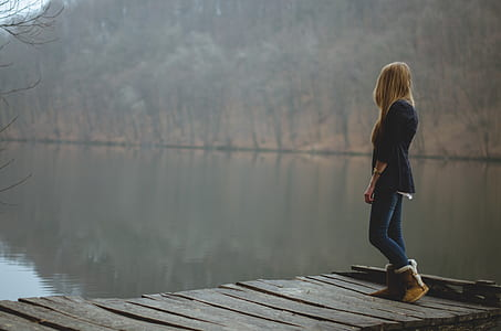 woman standing in wooden pier near lake