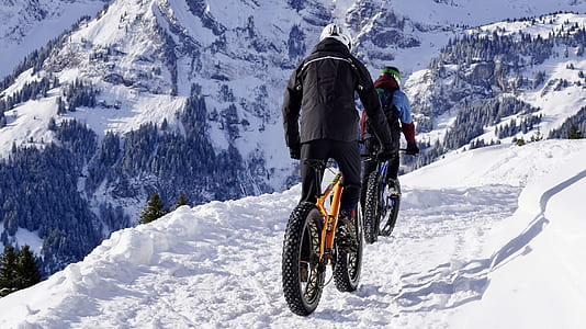 man riding yellow fat bike on snow-covered road