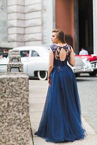 woman wearing blue dress standing on pavement