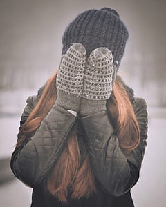 woman covering her face wearing winter gloves