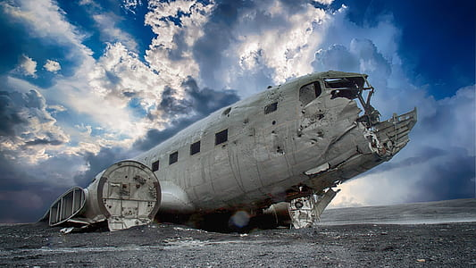 wrecked airplane under blue sky and white clouds during daytime