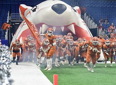 Football Team Running Thru Football Field