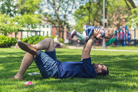 selective focus photography of man holding baby while lying on grass