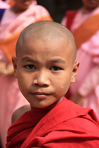 selective focus photography of boy in red monk dress
