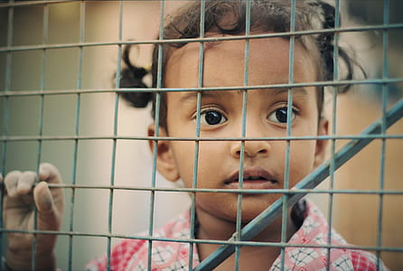 girl holding on gray metal wire fence
