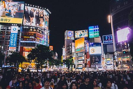 People Standing Near Buildings Under Night Sky