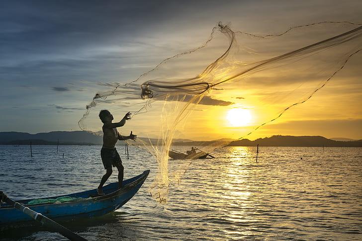 man on boat throwing fish net