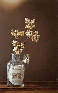 white and brown berries on clear glass bottle